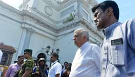 Sri Lankan Prime Minister Ranil Wickremasinghe (2nd R) arrives to visit the site of a bomb attack at