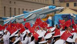 Chinese People's Liberation Army (PLA) Navy soldiers wave Chinese flags next to a model of a militar