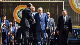 Palestinian president Mahmoud Abbas (C) is greeted upon his arrival at the Arab League headquarters