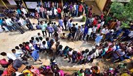 People wait in queues to cast their votes at a polling station during the third phase of general ele