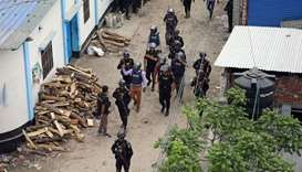 Security personnel walk near a militant den in the Bosila area where militants were killed in Dhaka