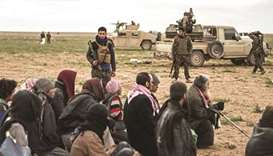 Men suspected of being Islamic State (IS) militants wait to be searched by members of the Kurdish-le