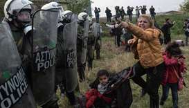 A woman clashes with Greek riot police outside of a refugee camp in Diavata