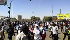 Sudanese protesters run for cover from teargas outside the military headquarters in the capital Khar