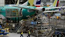 Employees walk by the end of a 737 Max aircraft at the Boeing factory in Renton, Washington, US