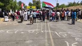 Sudanese protesters raise a national flags and chant slogans as they rally in front of the military