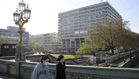 A woman wearing a mask is seen outside of St Thomas' Hospital as the spread of the coronavirus disea