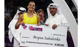 Belarus' Aryna Sabalenka is presented with a cheque after winning the Qatar Total Open 2020 at the K