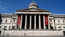 A woman walks outside the National Gallery in an empty Trafalgar Square in central London