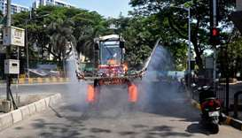 Municipal workers spray disinfectant along a street during a government-imposed nationwide lockdown
