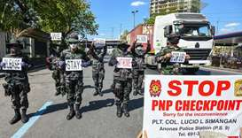 Police personnel hold up placards reminding people to stay at home amid concerns of the spread of th