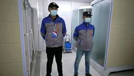 Security personnel wearing face masks stand guard near closed shower rooms inside the Leishenshan Ho