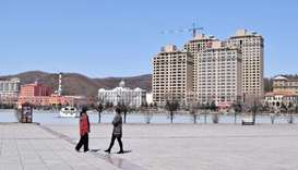 People wearing face masks are seen at a park in Suifenhe, a city of Heilongjiang province on the bor