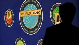 A man is silhouetted against the logo of the World Bank at the main venue for the International Mone