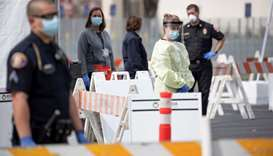A health worker in protective gear waits to hand out self-testing kits in a parking lot of Rose Bowl