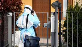 A doctor in protective suit visits the home of a person suffering from the coronavirus disease (COVI