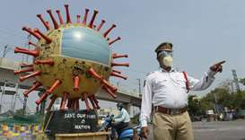 A traffic officer stands beside a coronavirus-themed globe at a traffic junction as he checks commut