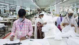 Bangladeshi garment workers make protective suit at a factory amid concerns over the spread of the c