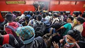 Migrant workers and their families board an overcrowded passenger train, after government imposed re