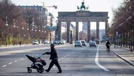 A woman pushing a pram crosses an almost deserted 17th June street near Brandenburger gate in Berlin