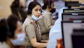 Police officers wearing protective masks work inside a call centre run by Uttar Pradesh state police