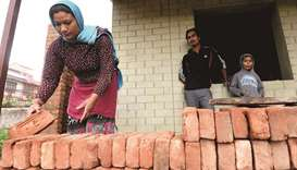 Husband and wife Rabindra (centre) and Anjana Tajale (left) work on the construction of their new tw
