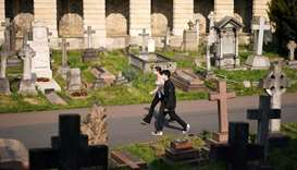 People wearing protective masks exercise in Brompton Cemetery, amid the coronavirus disease (COVID-1