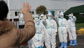 Medical personnel in protective suits wave hands to a patient who is discharged from the Leishenshan