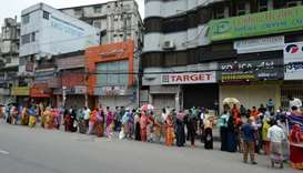 People queue to collect subsidised food items during a government-imposed nationwide lockdown as a p