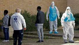 Medical staff stand next to asylum seekers evacuated from a hostel as they arrive to be tested for t