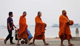 Buddhist monks wearing protective face masks walk to collect alms at an almost empty beach, which is