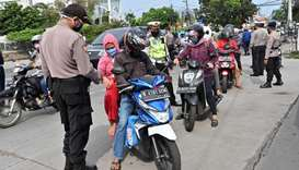 Indonesian policemen check the IDs of motorists at the border between Jakarta and Tangerang after th