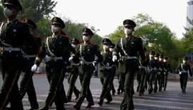 Chinese paramilitary police officers wear protective masks as they march through the street, while t