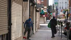 A private security guard wearing a face mask stands next to closed stores in the Fashion District in