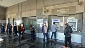 Libyans wearing protective face masks queue inside a bank in the centre of the capital Tripoli on Ap