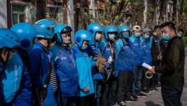 Delivery workers (L) wearing face masks amid the COVID-19 coronavirus pandemic listen to instruction