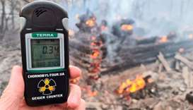 A geiger counter measures a radiation level at a site of fire burning in the exclusion zone around t