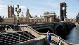 A general view of people wearing protective face mask's on steps by Westminster bridge as the spread