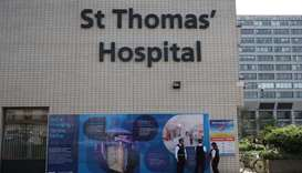 Police officers stand on duty outside St Thomas' Hospital in central London on April 7, 2020, where