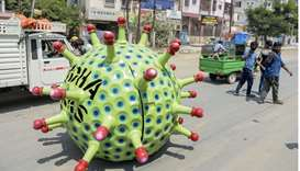 People take photos as inventor Sudhakar Yadav (inside) leads his coronavirus-themed made car on a ro