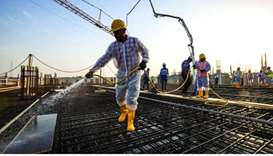 Construction workers are seen at the Al Thumama Stadium
