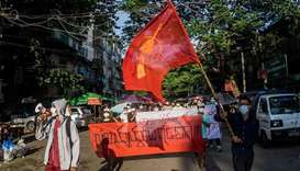 Protesters march during a demonstration against the military coup in Yangon on 11 April, 2021. (AFP)