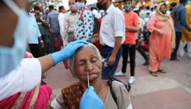 A devotee reacts as a health worker collects a swab sample, on the banks of the Ganges river during