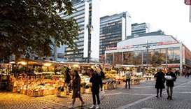 People walk past market stalls at Hotorget square, amid the outbreak of the coronavirus disease (Cov