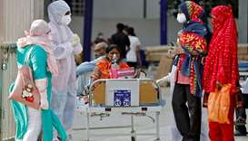 Patients sit on bed waiting to be moved to a hospital, amidst the spread of the coronavirus disease