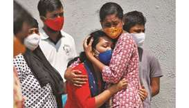 A woman whose husband died due to coronavirus is consoled outside a Covid-19 hospital mortuary in Ah