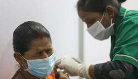 A woman reacts as she receives a dose of Covishield a coronavirus disease vaccine manufactured by Se
