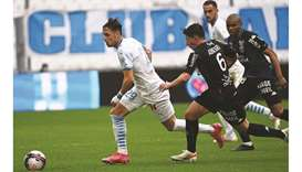 Marseille's Pol Lirola (left) vies for the ball with Lorient's Laurent Abergel (centre) during the F