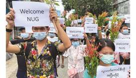Anti-government protesters hold placards to show their support and welcome the new National Unity Go