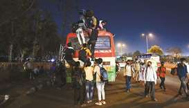 People climb up on the roof of a bus at a bus station in New Delhi yesterday, to leave for their nat